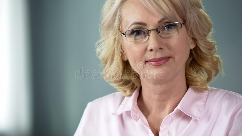 Senior lady with kind eyes and pleasant smile looking into camera inducing trust. Stock photo royalty free stock image