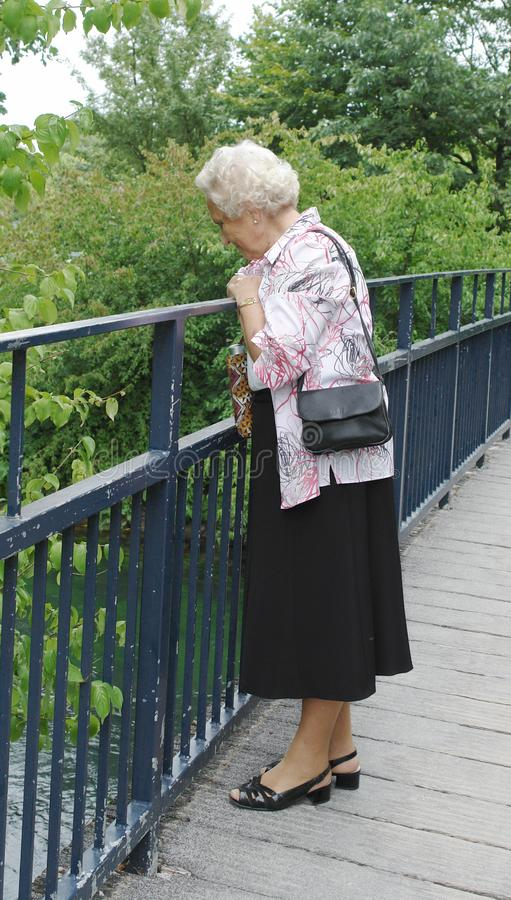 Senior Lady Looking Into River Free Stock Photo