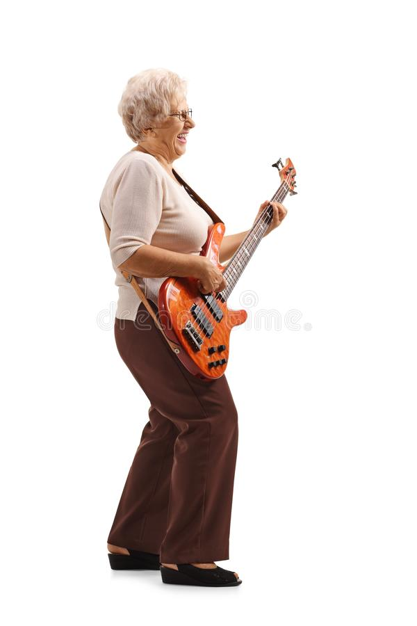 Senior lady playing an electric guitar. Full length shot of a senior lady playing an electric guitar isolated on white background royalty free stock images