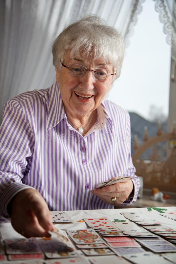Senior lady playing solitaire cards at home stock image