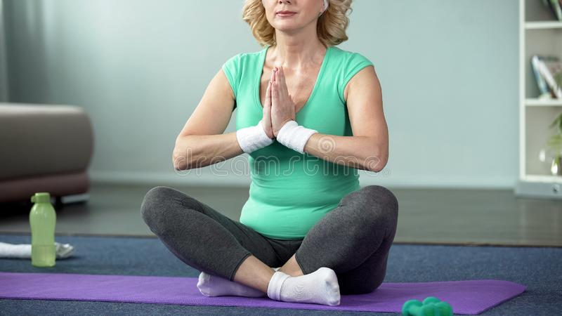 Senior lady practicing yoga at home, wellness and health care, active recreation royalty free stock photo