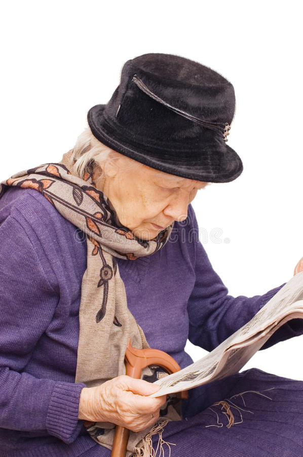 Senior lady reads the newspaper stock images