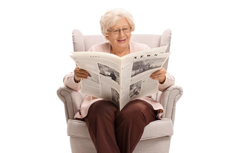 Senior lady sitting in an armchair and reading a newspaper. Isolated on white background royalty free stock photography