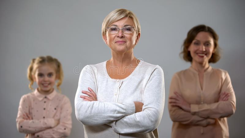 Senior lady standing with crossed arms, daughter and granddaughter on background royalty free stock photos