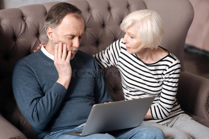Senior lady supporting her husband having toothache stock photography