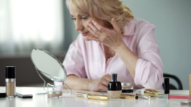 Senior lady touching her face after applying moisturizing cream, appearance. Stock photo stock photos