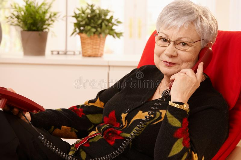 Senior lady using landline phone. Sitting in living room armchair, looking at camera stock images