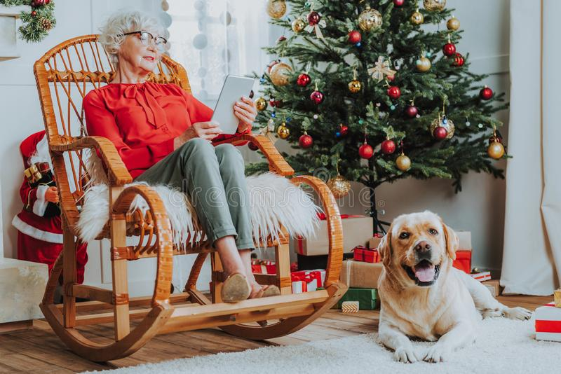 Old woman is sitting in chair at home royalty free stock photos
