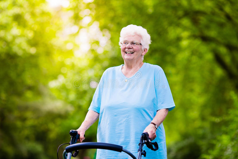 Senior lady with a walker. Happy senior handicapped lady with a walking disability enjoying a walk in a sunny park pushing her walker or wheel chair, aid and stock photography