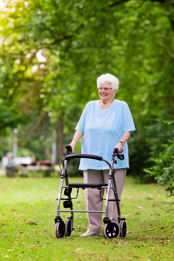 Senior lady with a walker. Happy senior handicapped lady with a walking disability enjoying a walk in a sunny park pushing her walker or wheel chair, aid and stock image