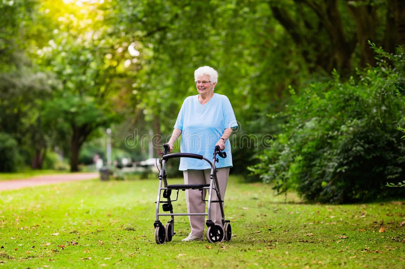 Senior lady with a walker. Happy senior handicapped lady with a walking disability enjoying a walk in a sunny park pushing her walker or wheel chair, aid and stock photo