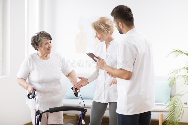 Senior lady with walker during physiotherapy with professional female doctor and male nurse. Grey senior lady with walker during physiotherapy with professional stock images