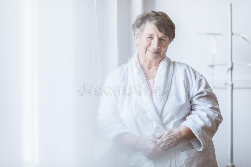 Senior lady wearing white bathrobe standing by the window at nursing home. Senior grey lady wearing white bathrobe standing by the window at nursing home royalty free stock photo