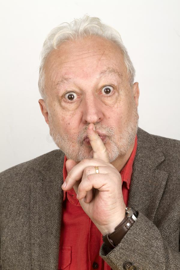Senior laying trigger finger on mouth royalty free stock images