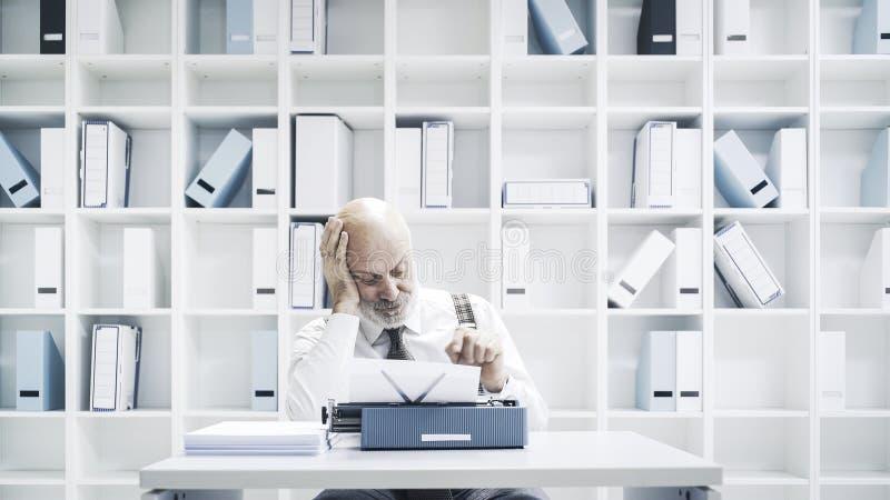Senior businessman working with a typewriter royalty free stock image