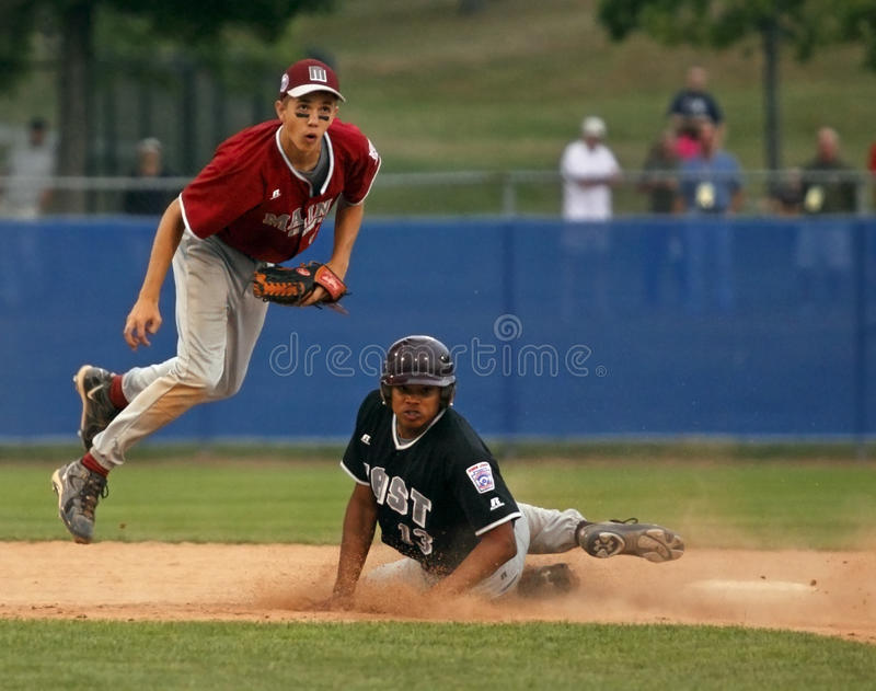 Senior league baseball world series leap. BANGOR, MAINE - AUGUST 18: Seth Freudenberger of Maine District 3 (Bangor East/West L.L.) leaps out of the way of a stock image