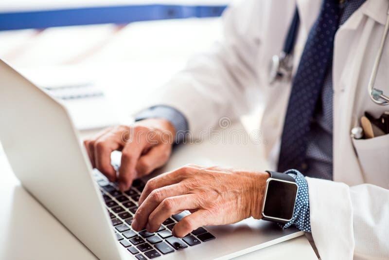 Senior lekarka z laptopem pracuje przy biurowym biurkiem zdjęcia stock