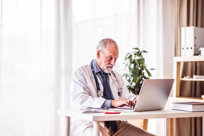 Senior lekarka z laptopem pracuje przy biurowym biurkiem obrazy royalty free