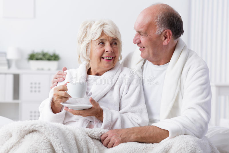 Senior lovers in bed. Romance in old age royalty free stock photography