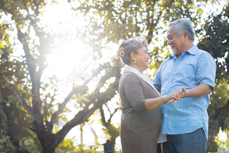 Senior lovers dance and smile at each other warmly. Happy life after retirement, Senior lovers dance and smile at each other warmly stock image