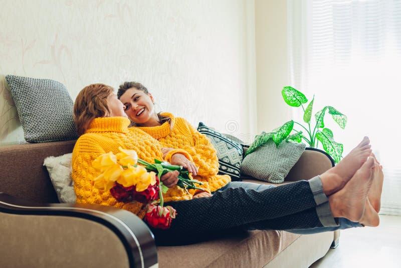 Senior macierzysty, jej dorosły córki obsiadanie na leżance i śmiać się w domu Macierzysty ` s dnia poj?cie zdjęcie stock