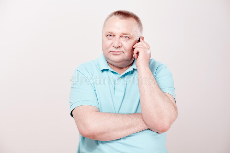 Senior making call. Mature man wearing blue shirt talking on mobile phone against white wall - communication concept royalty free stock photos