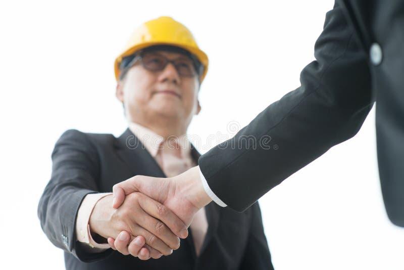 Senior male architect hand shaking. Senior male architects with hardhat hand shaking stock image