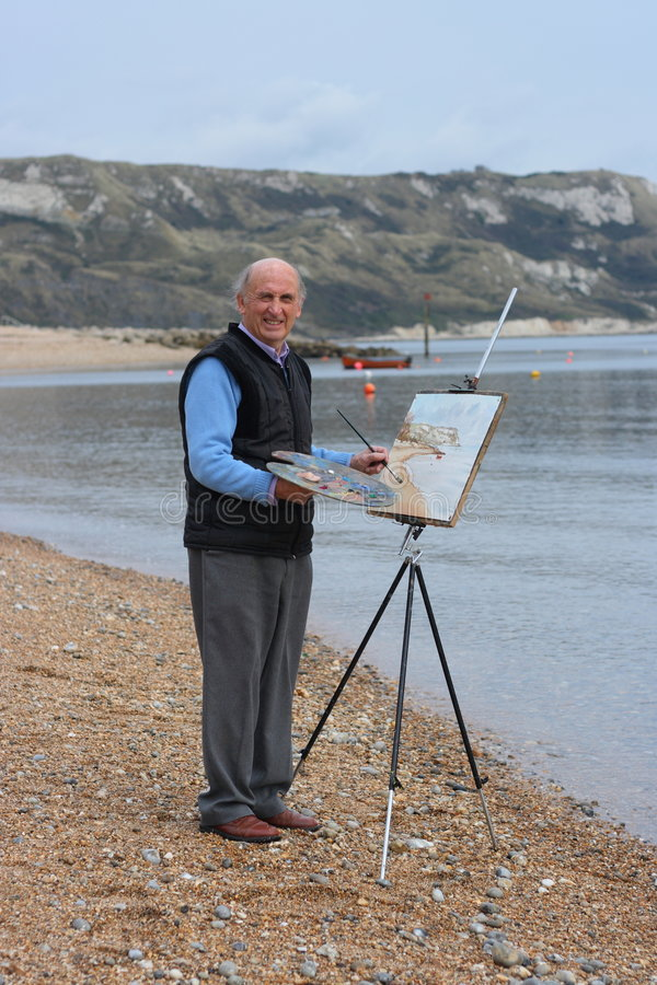 Senior male artist painting by the sea. royalty free stock photography