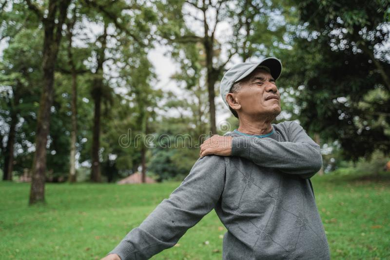 Senior male asian having sore shoulder and pain on his joints royalty free stock images
