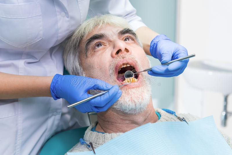 Senior male with bad teeth. Examination at the dentist. Dental diseases curing methods stock photos