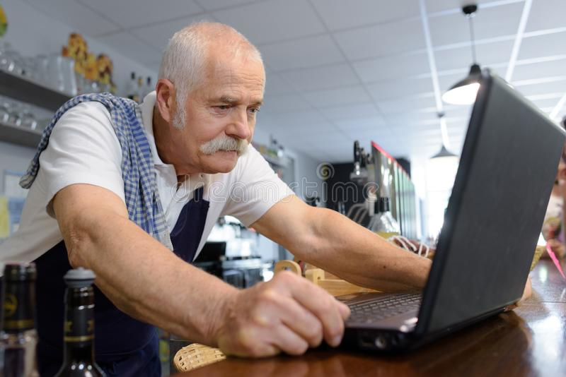 Senior male barista looking at laptop. Information stock photo