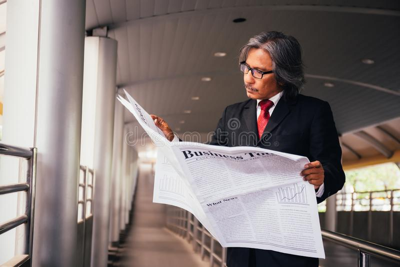 Senior male business executive reading traditional newspaper outside the company. stock photos