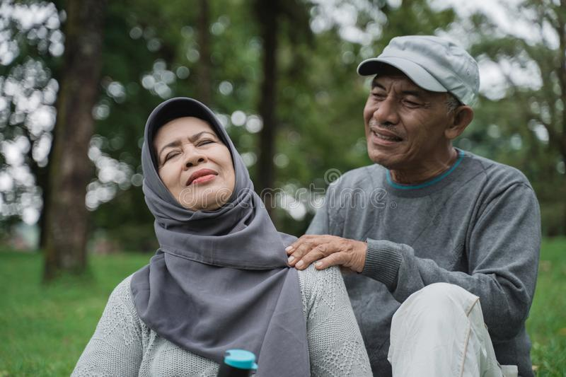 Senior male couple giving some massage on shoulder and neck to his wife royalty free stock photography