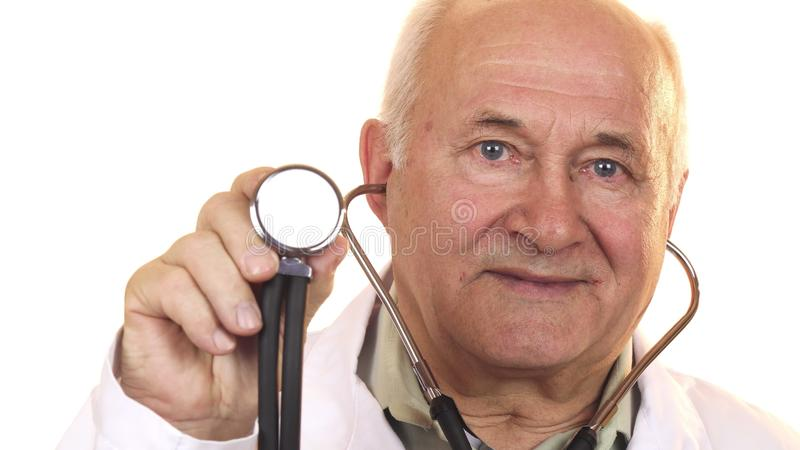 Senior male doctor holding up a stethoscope to the camera royalty free stock photography