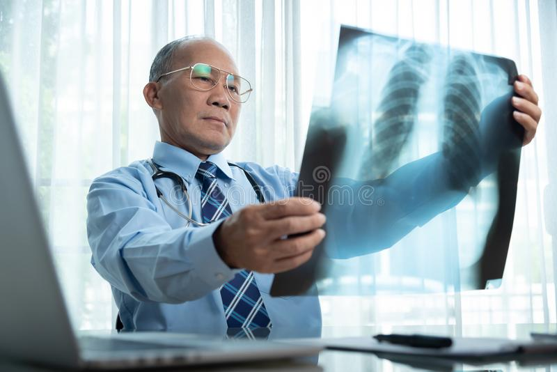 Senior Male doctor looking to x-ray film. royalty free stock photos
