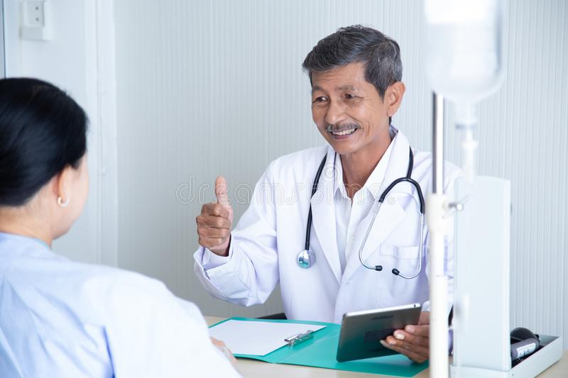 Senior male doctor smile discussing with  speaking with his senior patient royalty free stock photo
