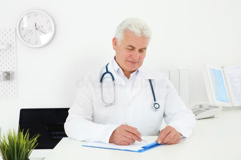 Senior male doctor working at reception desk. In hospital royalty free stock photos