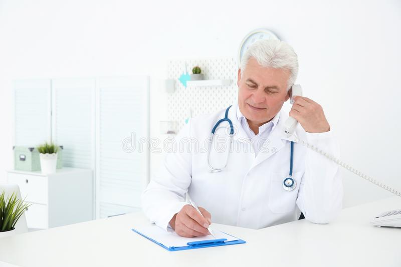 Senior male doctor working at reception desk. In hospital stock image