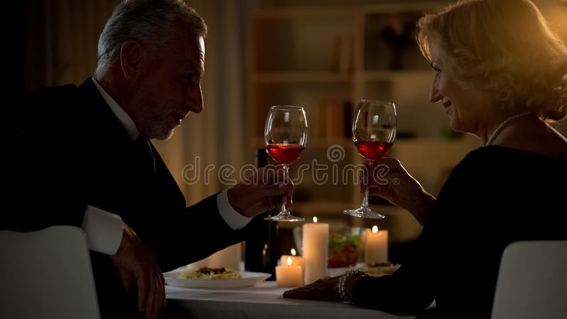 Senior male and female toasting with wine glasses, aged couple flirting on date royalty free stock photo