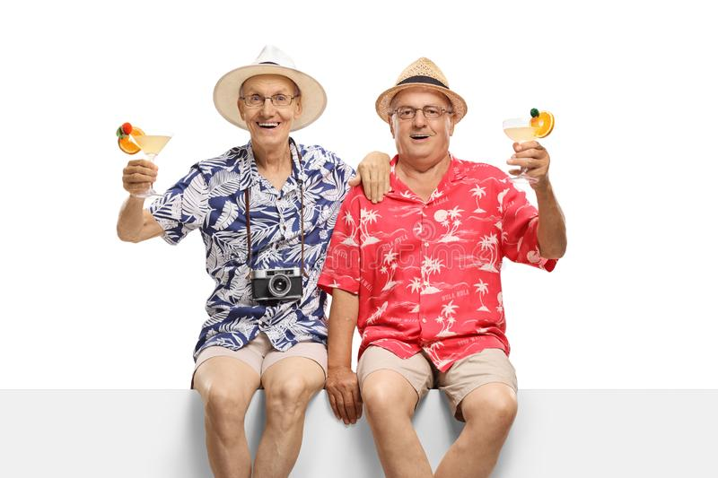 Senior male friends with cocktails sitting on a panel royalty free stock photos