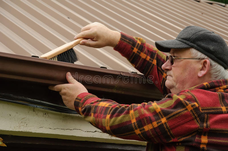 Senior male gutter. Senior male cleaning out the shed gutter with brush royalty free stock photos