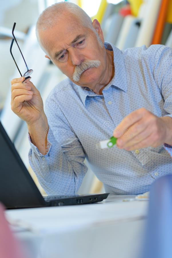 Senior male with laptop and external hard drive stock photography