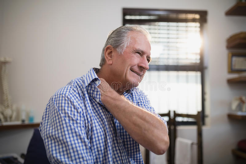 Senior male patient grimacing with neck pain stock images
