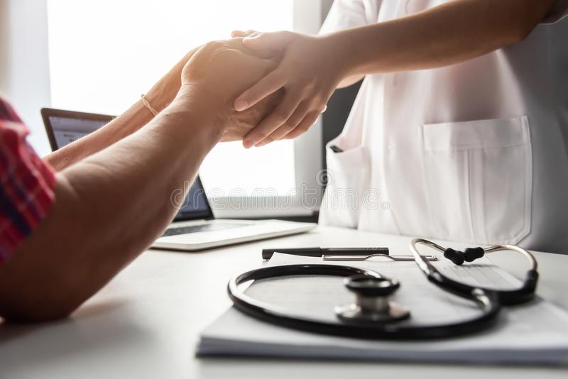 Senior male patient handshaking with Doctor female. royalty free stock photography