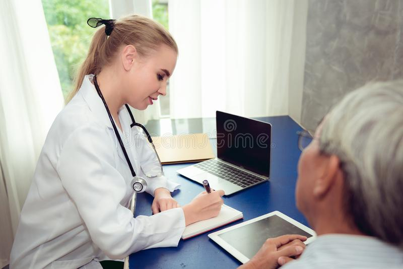 Senior male patient having consultation with female doctor in ex royalty free stock photos