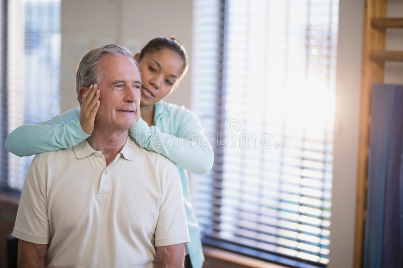 Senior male patient receiving neck massage from female therapist. At hospital ward stock image