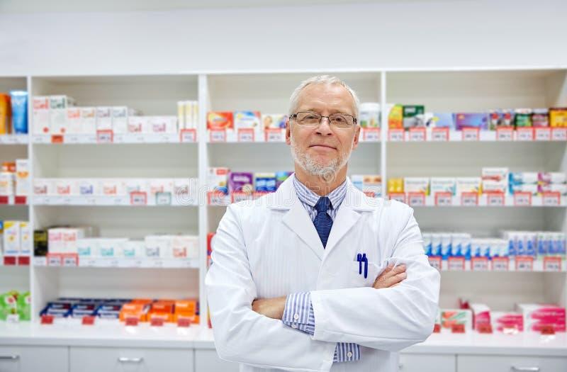 Senior male pharmacist in white coat at drugstore. Medicine, pharmacy, people, health care and pharmacology concept - smiling senior male pharmacist in white stock image