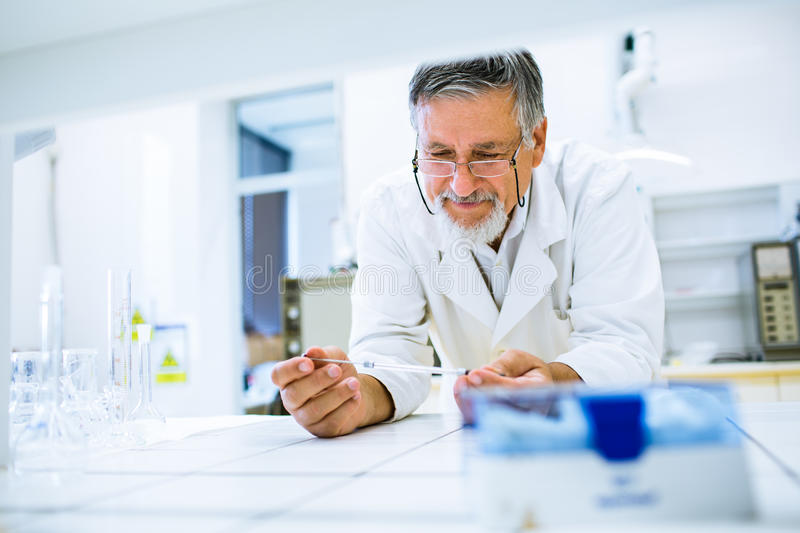 Senior male researcher carrying out scientific research in a lab. (shallow DOF; color toned image royalty free stock photography