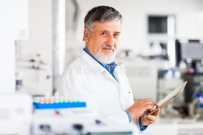 Senior male researcher carrying out scientific research in a lab. (shallow DOF; color toned image royalty free stock photos