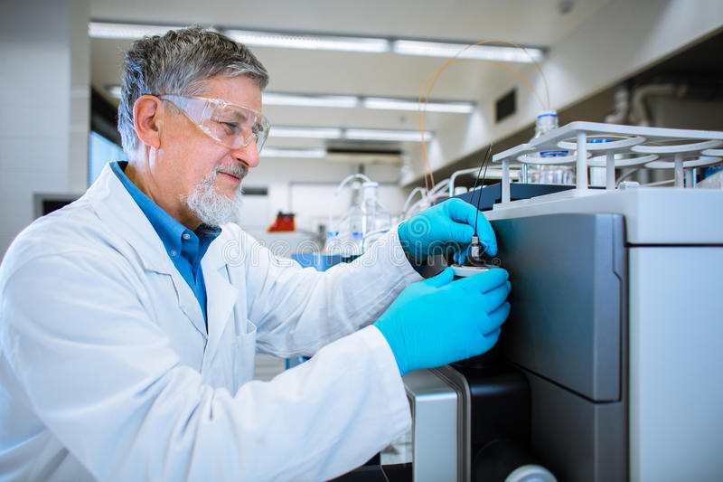 Senior male researcher carrying out scientific research in a lab. (shallow DOF; color toned image stock photos